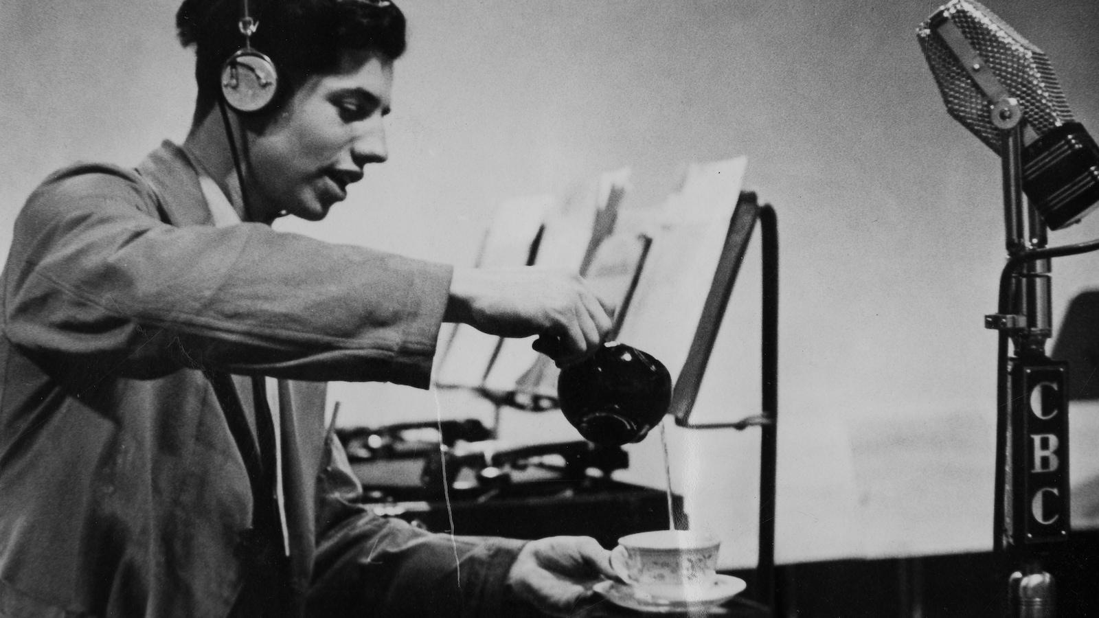 Un homme avec des écouteurs verse de l'eau d'une théière dans une tasse devant un microphone.