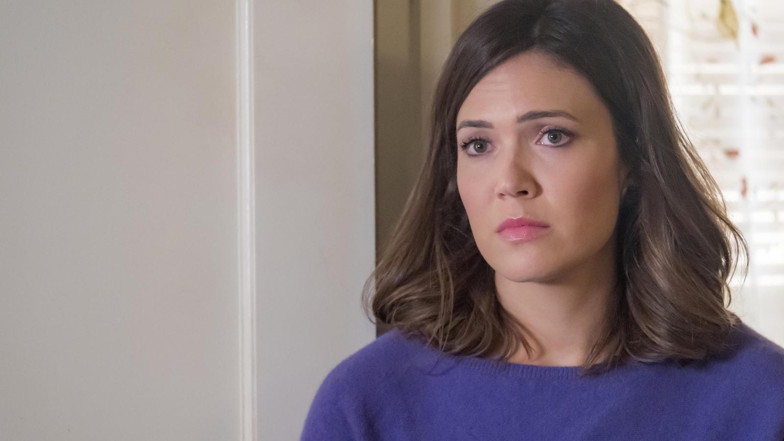 Elle porte un chandail violet.