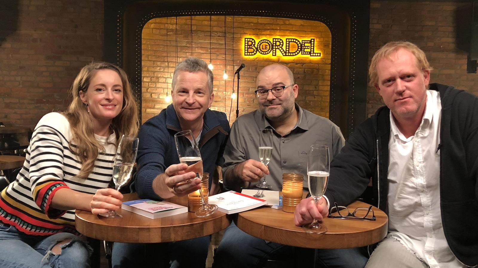 L'animateur et ses invités assis à une table au bar le Bordel