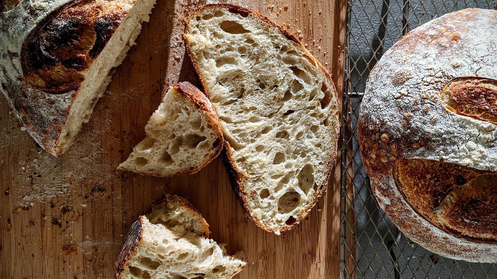 Une miche de pain frais tranchée sur une planche de bois.