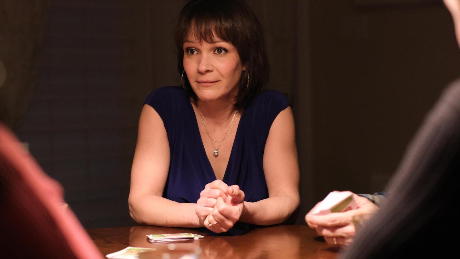 La femme est assise et à les bras posés sur une table.