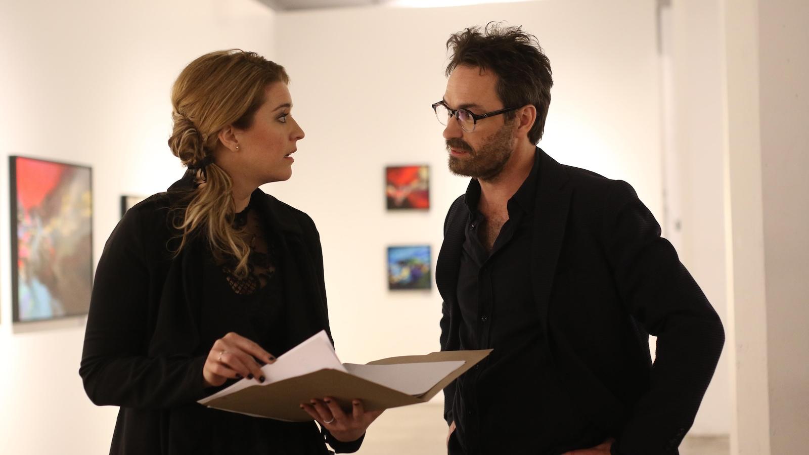 Une femme discute avec un homme dans une galerie d'art.