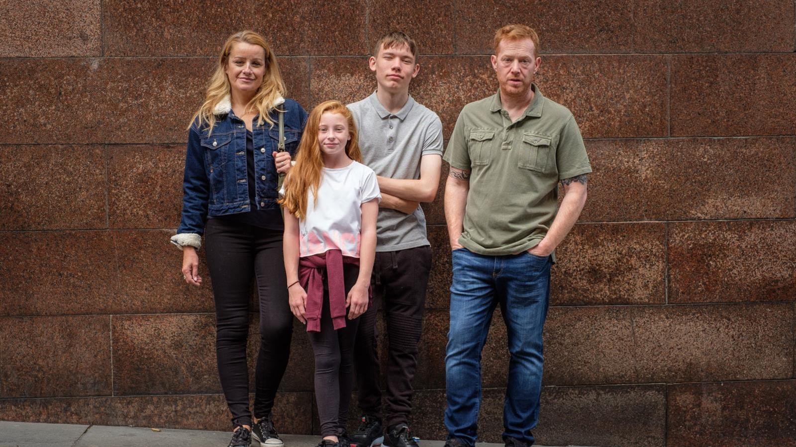 Une famille pose devant un mur en briques.