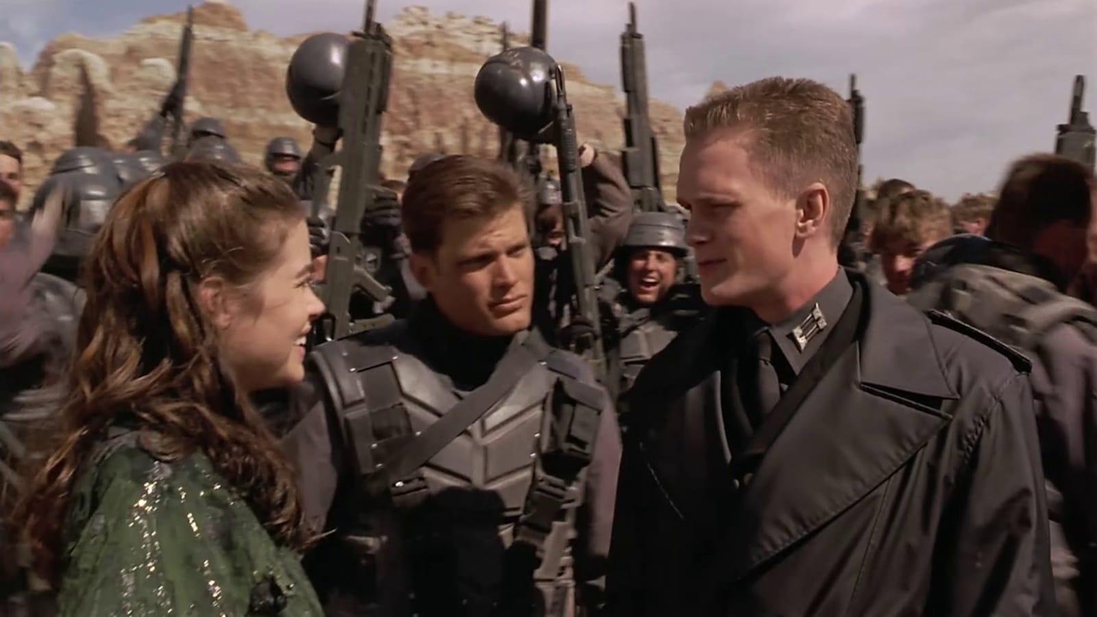 Une jeune femme parle à un jeune soldat, entouré d'autres hommes en tenues de combat.