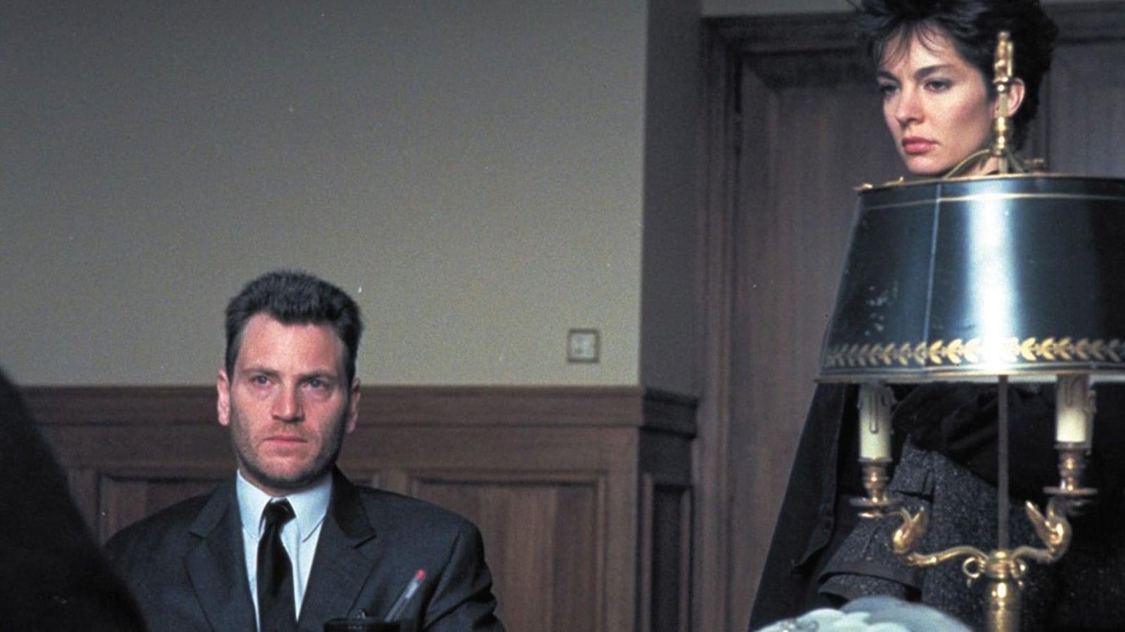 Tchéky Karyo est assis, Anne Parillaud est debout, les deux sont devant un bureau.