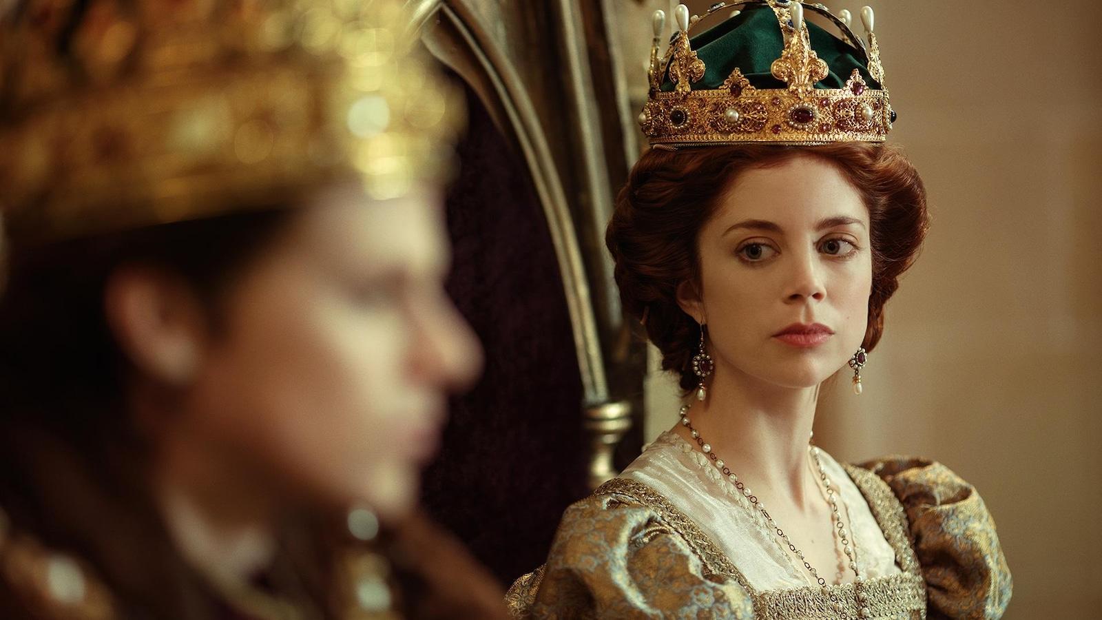 Une femme avec une couronne sur la tête regarde une autre.