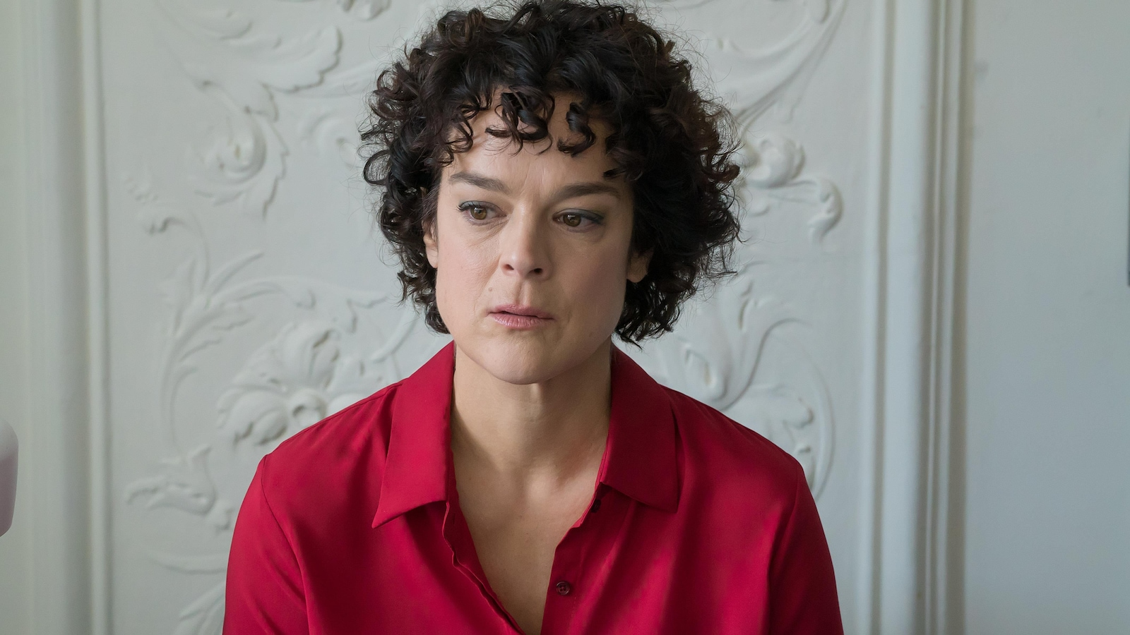 Tina est une femme aux cheveux frisés bruns. Elle porte un chemisier rouge.