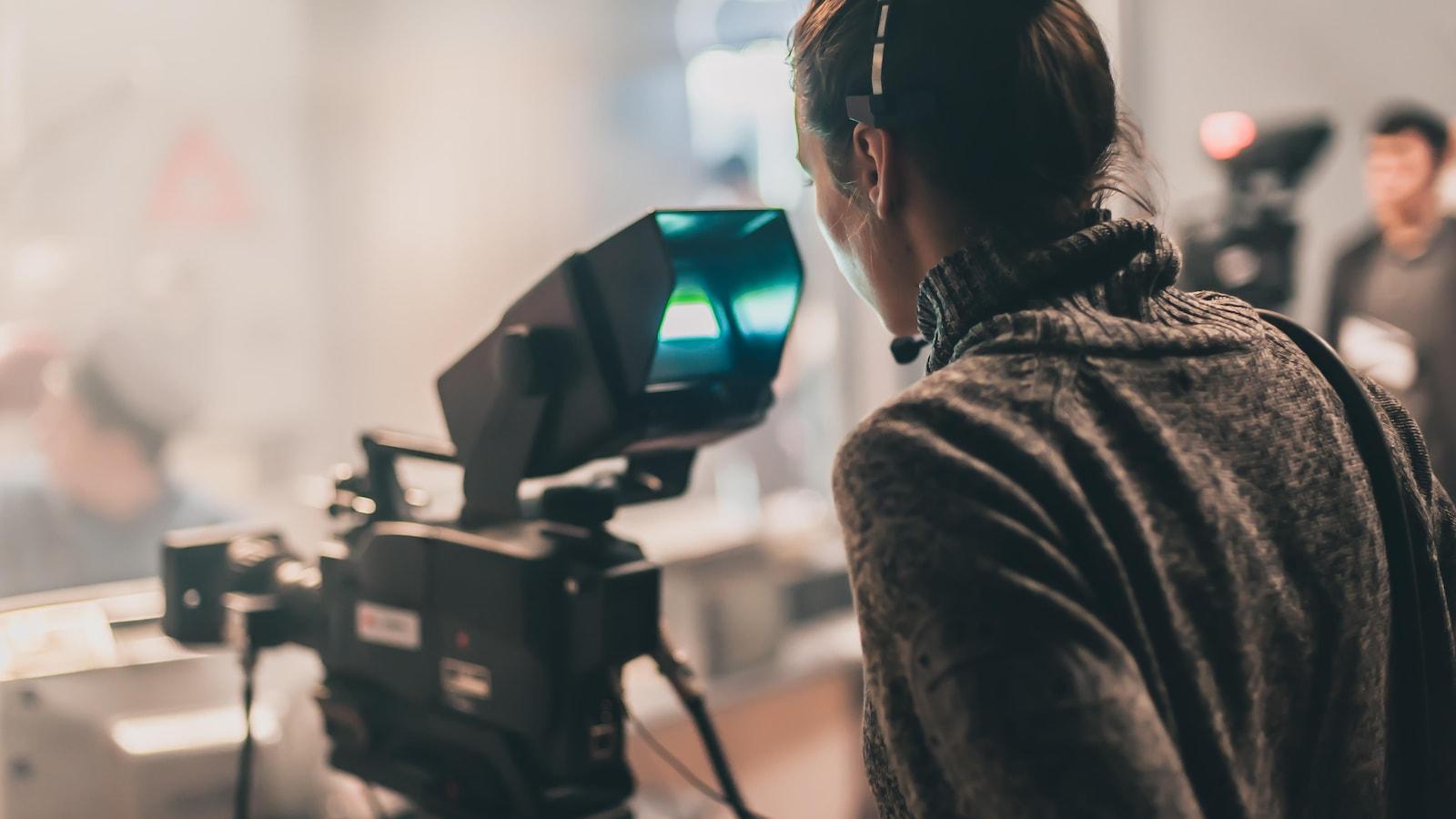 Une femme se tient derrière une caméra.