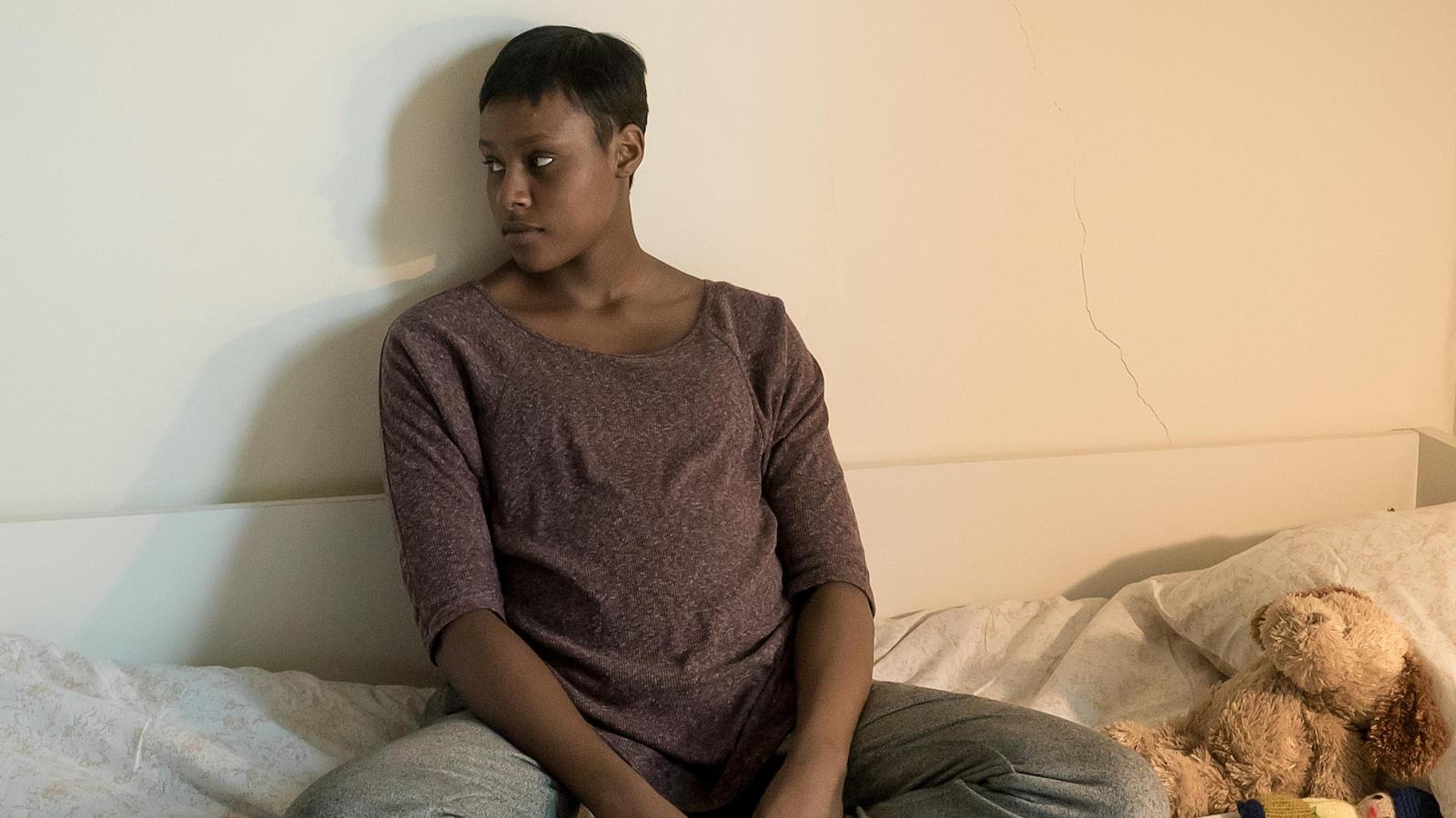 Edwidge (Naïla Victoria Louisdort-Biassou) est assise les jambes croisées sur son lit.