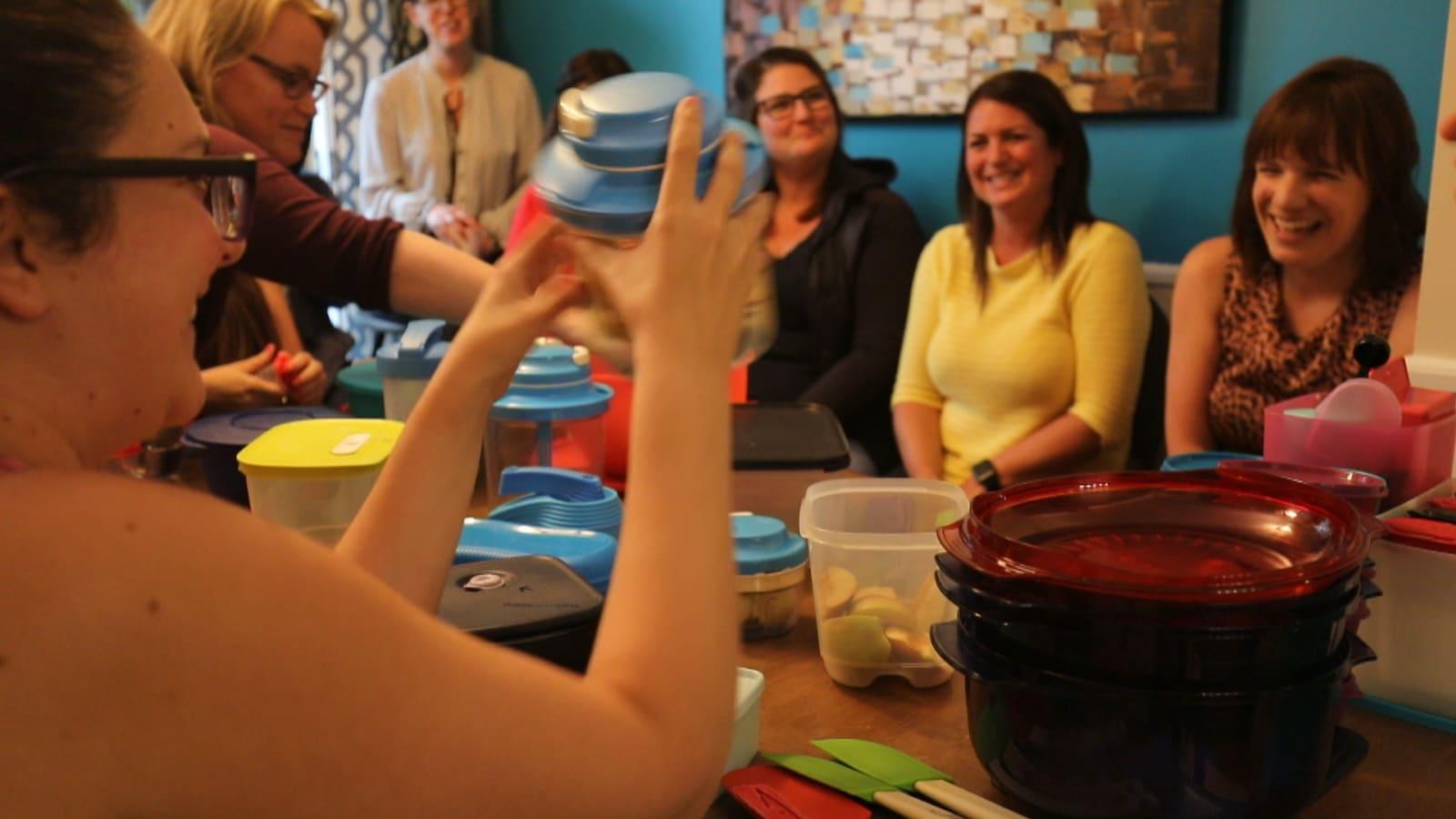 Des femmes autour d'une table avec des Tupperware sur la table.
