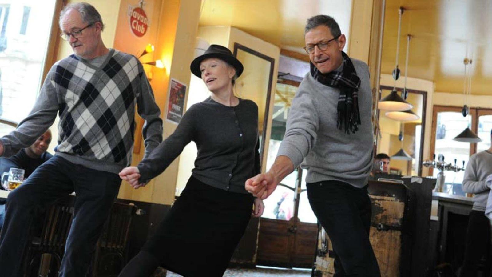 Dans un café parisien, deux hommes et une femme portant un chapeau esquissent un pas de danse.