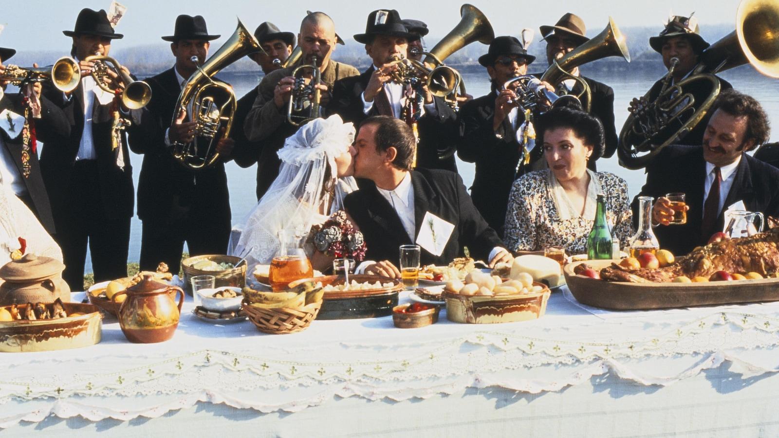 Un couple de mariés assis à table s'embrasse devant une fanfare.