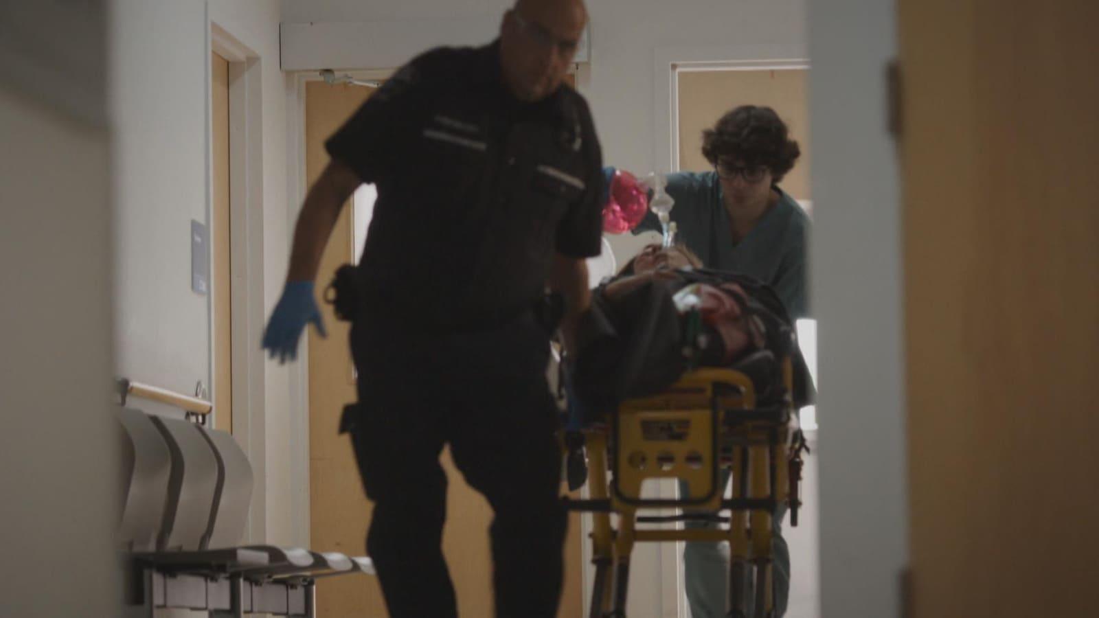 Un infirmier (Thomas Postigo) et un ambulancier pousse une civière dans le corridor de l'hôpital.