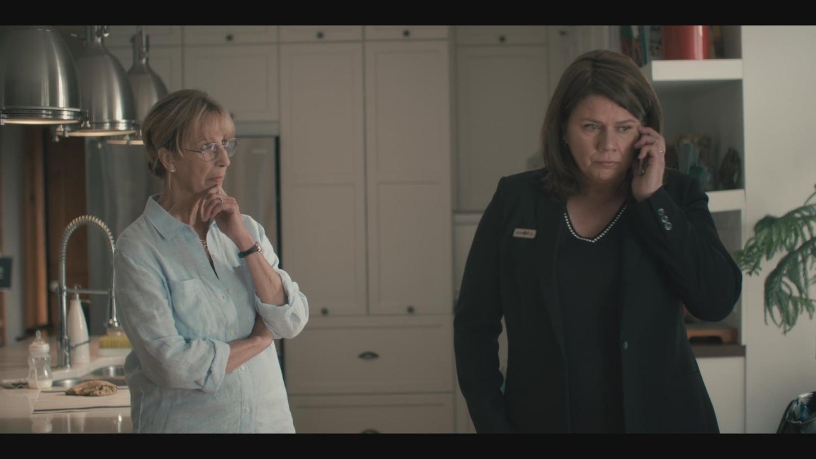 Une femme regarde l'autre qui parle au téléphone.