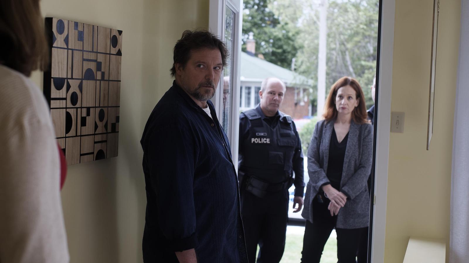 Une femme devant la porte attend un homme qui sort de la maison et regarde derrière lui.