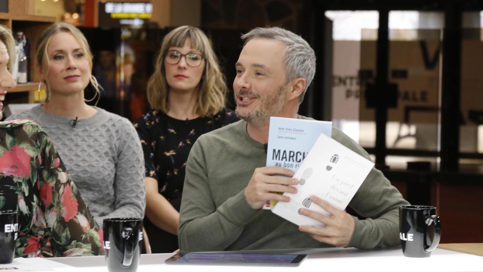 Le chroniqueur tient des livres dans ses mains.