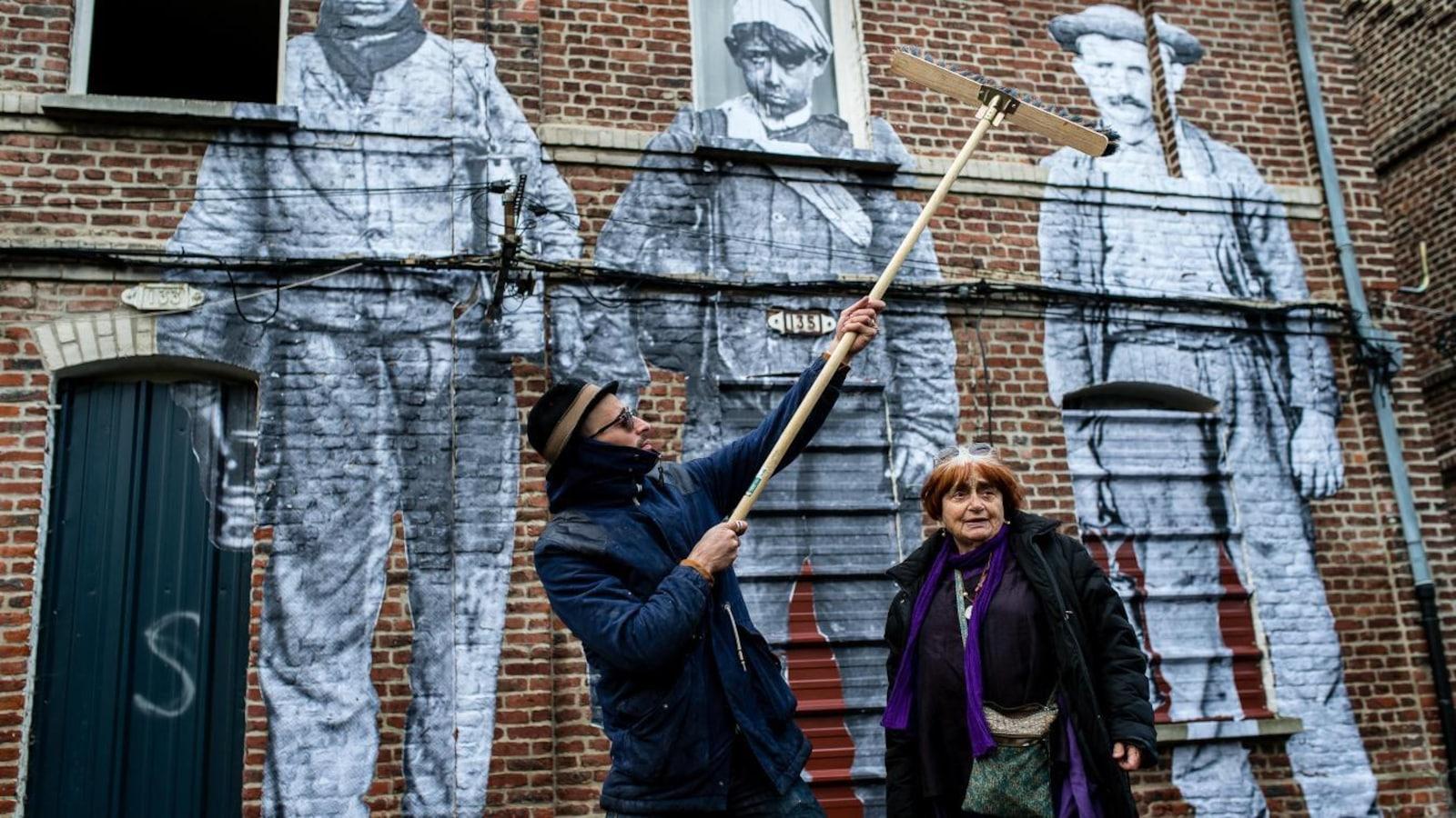 Un homme avec un grand balai colle des photos sur un mur en briques, une femme à ses côtés regarde.
