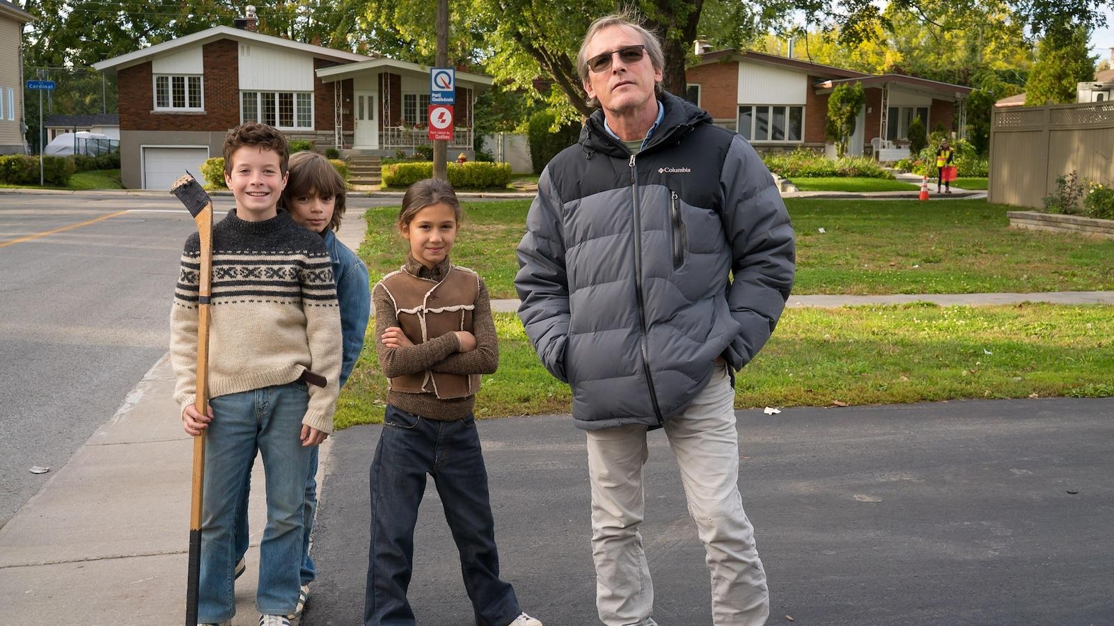 Le réalisateur Louis Bélanger à côté de trois enfants, dans une rue.