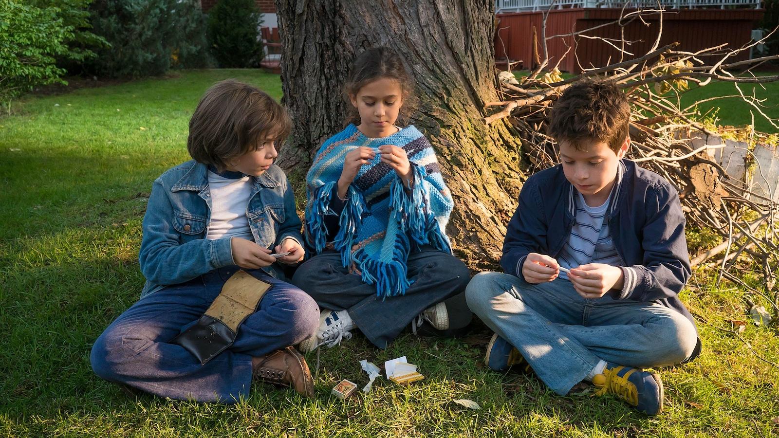 Trois enfants assis au pied d'un arbre.