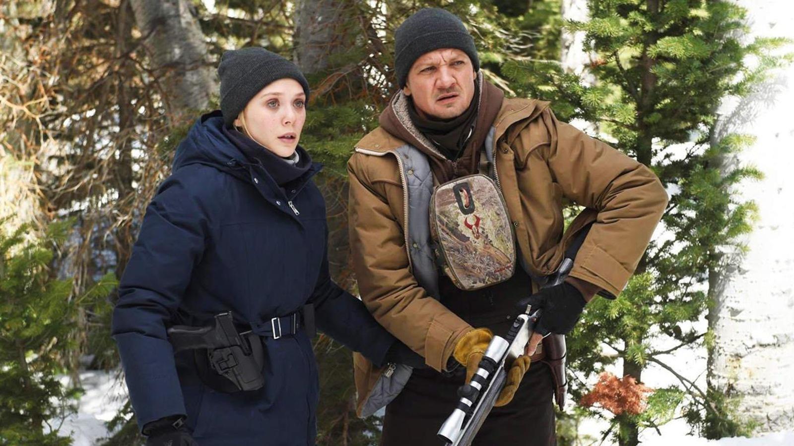 Une femme et un homme, armés, en tenues d'hiver, dans une forêt.