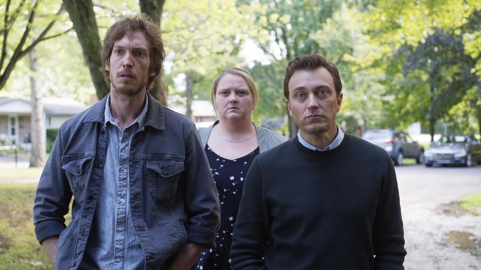 Les deux hommes et la femme au centre regardent au loin.