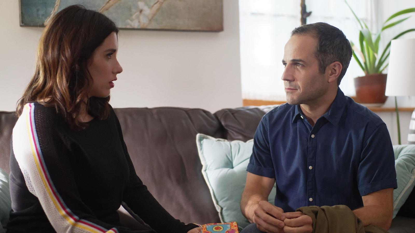 Une femme et un homme se regardent, assis sur un divan.