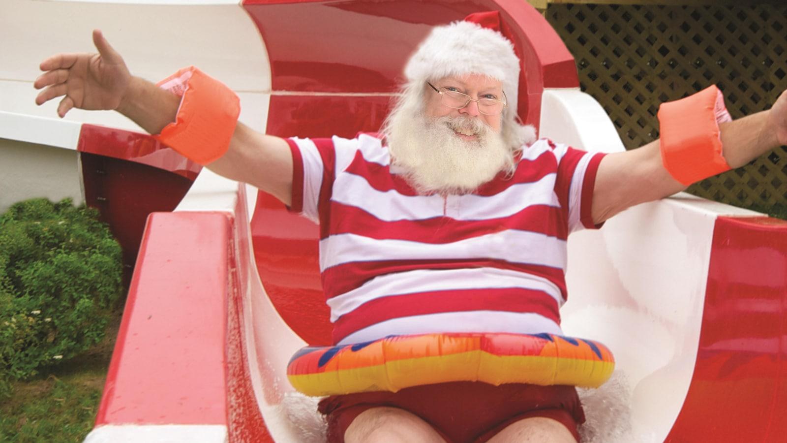 Le père Noël glisse dans une glissade d'eau, une bouée autour du ventre.