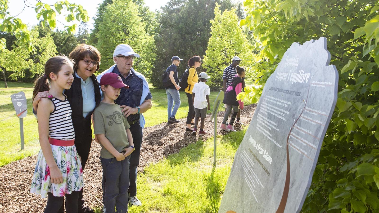 Sur le sentier du Jardin botanique, une famille lit un panneau explicatif de l'exposition.