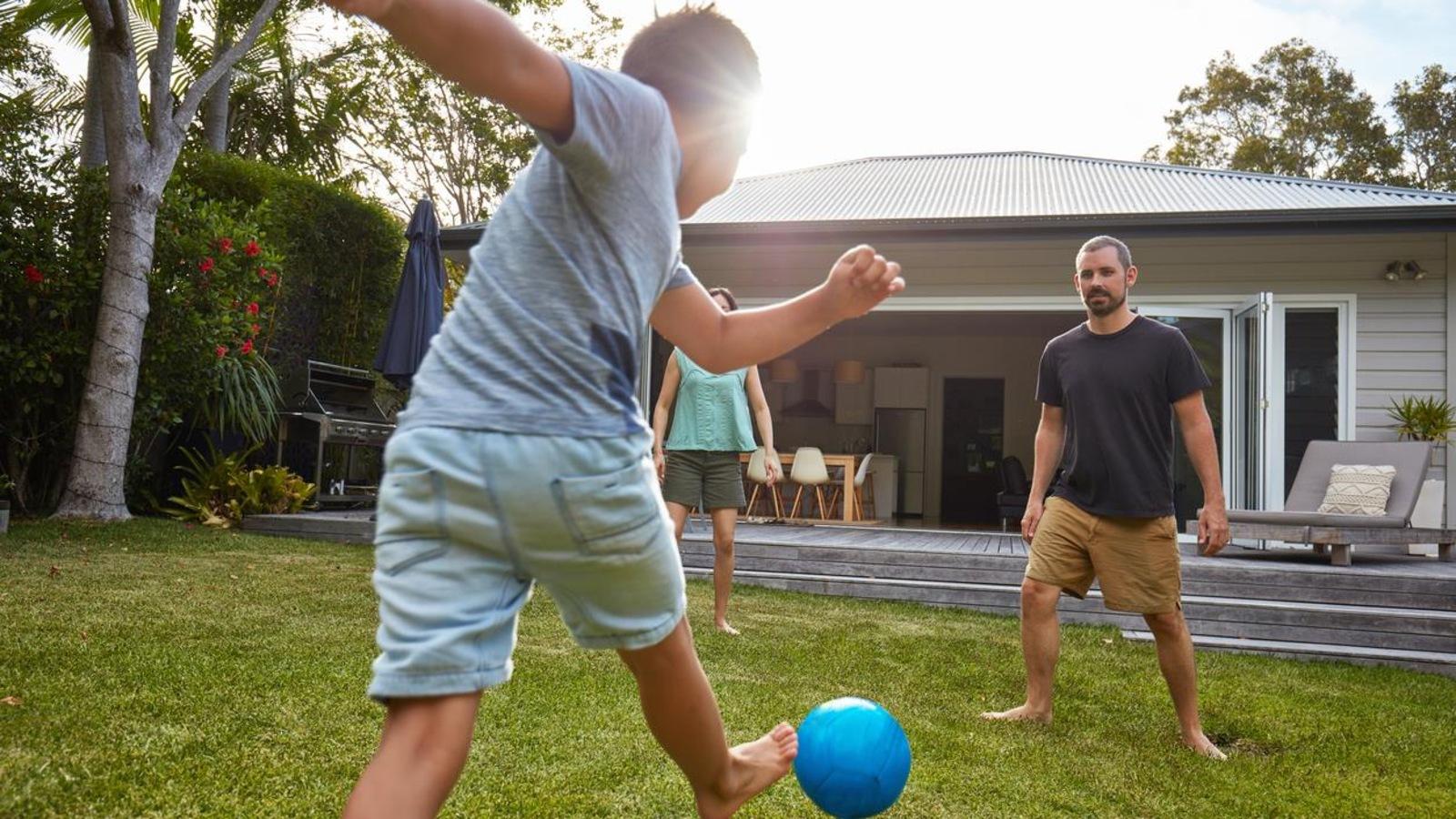Un jeune garçon s'amuse avec un ballon aux côtés de ses parents.