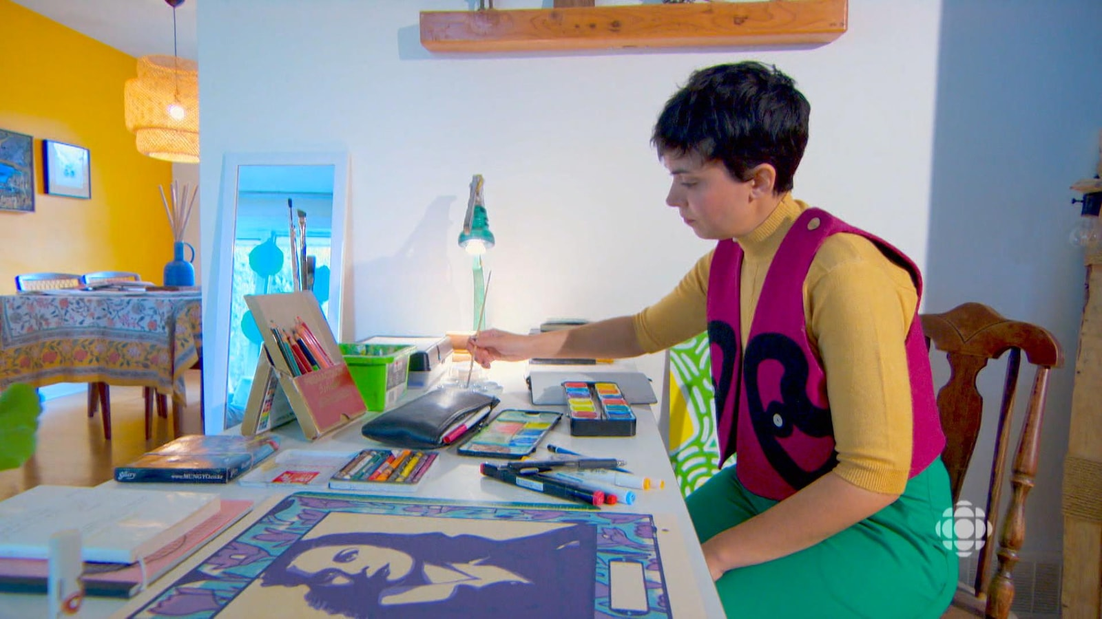 Zoé peint à son bureau dans sa maison.