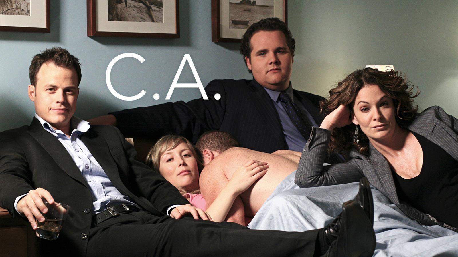 Une personne est nue, sur une autre alors que trois autres personnes habillées, sont assis sur le lit.