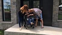 Alek dans son fauteuil entouré de ses parents devant leur maison à Val-des-Monts.