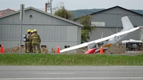 Un petit avion blanc, avec des motifs rouges et orange, a le nez vers le sol. L'appareil est près du bord de la route et des pompiers le regardent.