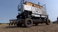 Un tracteur robotisé arrêté au milieu d'un champ.