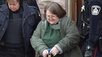 Elizabeth Wettlaufer excortée par deux agents de police.