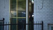 Un policier entre par la porte vitrée de l'immeuble où résidait Amor Ftouhi, accusé d'avoir poignardé un policier aux États-Unis.