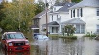 Des voitures sont sous l'eau dans un quartier résidentiel inondé.