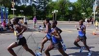 Des meneurs du marathon d'Ottawa courent dans la rue.