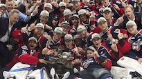 Des joueurs de hockey prennent une photo de groupe avec la coupe