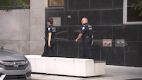 Des policiers portant des pantalons et des t-shirts bleu marin et une veste pare-balle sur lequel on peut lire « police ».
