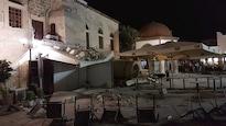 Des gens se trouvent sur une place publique située près d'un bâtiment endommagé à la suite d'un tremblement de terre qui a ravagé l'île de Kos, en Grèce, dans la nuit du 21 juillet 2017.