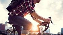 Gros plan d'un cycliste en train de pédaler sur son vélo, avec des gratte-ciels et un coucher de soleil en arrière-plan.