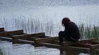 Une adolescente est assise sur un quai