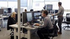 Des employés à leur poste de travail dans un espace ouvert.