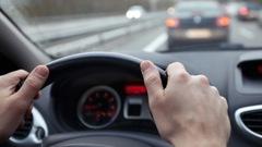 Des mains sur un volant dans une voiture.