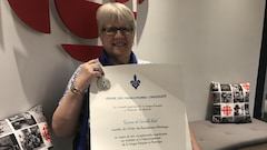 Une femme tient un document officiel devant un logo de Radio-Canada