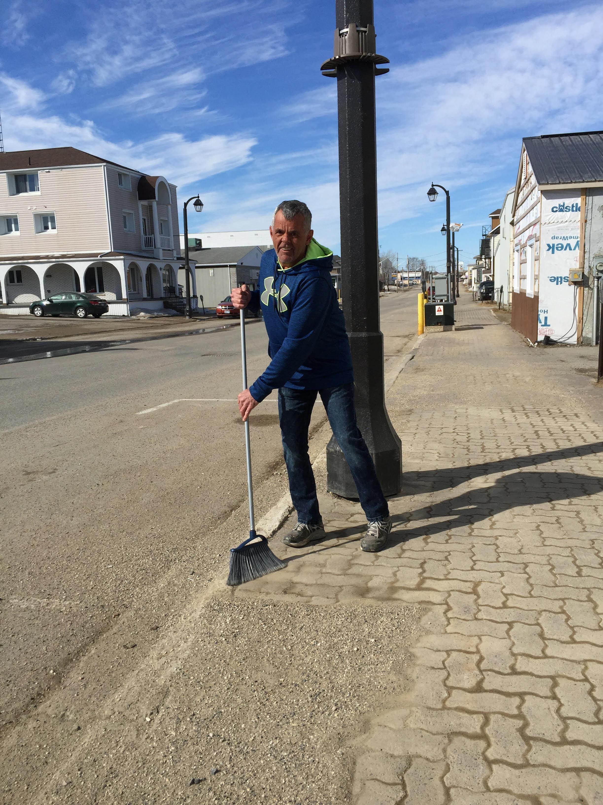 Un homme passe le balai dans une rue.