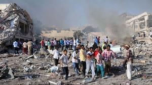 Des gens transportent le corps d'un homme tué lors du double attentat.