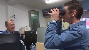 Un homme avec un appareil de lecture de la rétine devant les yeux et un autre homme devant lui