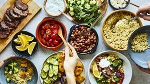 Tablée avec des bol-repas à assembler : choix de boeuf, tomates, courgettes, orzo, tzatziki, etc.